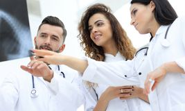 Group of medical workers looking at patient`s x-ray film Stock Images