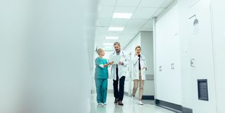 Group of medics with clipboard walking along hospital corridor. Doctor and nurse discussing medical report with female colleague talking on mobile phone Royalty Free Stock Photography