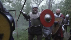 Group of medieval soldiers rush into the battle with battlecry
