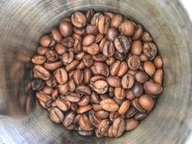 Group of medium roasted coffee bean in stainless steel cup stock photography