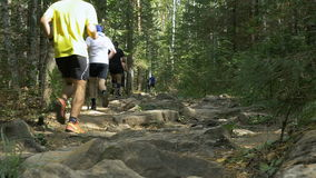 Group of men athletes run one behind other on a mountain trail among rocks stock video footage