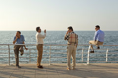 A group of men, Beirut. A group of men two stood, one leaning and one sat on the railings, Beirut Waterfront, Lebanon Stock Photography