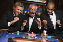 Group of men celebrating win at roulette table. In casino royalty free stock image
