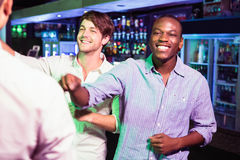 Group of men dancing near bar counter Stock Images