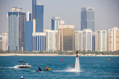 Group of men doing water sports in front of skyline taken on March 31, 2013 in Abu Dhabi, United Arab. ABU DHABI - MARCH 31, 2013: Group of men doing water Royalty Free Stock Photos