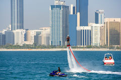 Group of men doing water sports in front of skyline taken on March 31, 2013 in Abu Dhabi, United Arab. ABU DHABI - MARCH 31, 2013: Group of men doing water Stock Photo
