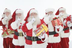 Group Of Men Dressed As Santa Claus Holding Gifts Stock Photo