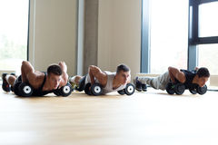 Group of men with dumbbells in gym Stock Images