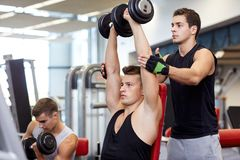 Group of men with dumbbells in gym Stock Photo