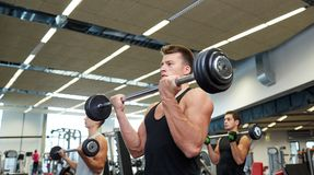 Group of men flexing muscles with barbell in gym Royalty Free Stock Photography