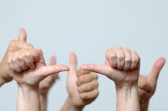Group of men giving a thumbs up gesture stock photo
