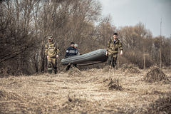 Group of men hunters in camouflage with rubber boat crossing dry rural field with bushes on background during spring hunting Stock Photography