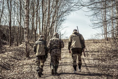 Group of men hunters going up on rural road during hunting season. Group of men hunters going up on rural road  in forest during hunting season Stock Photography