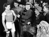 Group of men looking at an athlete Stock Image