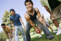 Group of men playing football in park low angle view. Stock Images