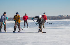 Group of men playing hockey on a frozen river Dnepr in Ukraine. Dnepr, Ukraine - January 22, 2017: Group of men playing hockey on a frozen river Dnepr in Ukraine stock photos
