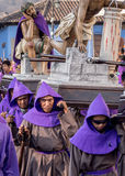 Antigua Easter Procession, Guatemala. A group of men in purple robes carry a large wooden holy scene as part of Semana Santa (Easter religious processions) in Royalty Free Stock Photography