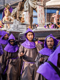 Antigua Easter Procession, Guatemala. A group of men in purple robes carry a large wooden holy scene as part of Semana Santa (Easter religious processions) in Royalty Free Stock Photos