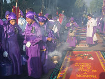 Holy Procession Antigua. A group of men in purple robes take part in a procession as part of Semana Santa (Easter religious celebrations) in Antigua, Guatemala Royalty Free Stock Image