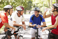Group Of Men Resting During Cycle Ride Through Park Stock Photography