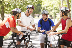 Group Of Men Resting During Cycle Ride Through Park Royalty Free Stock Image