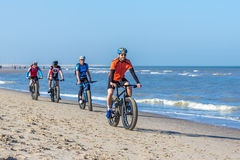 Group of men riding bikes on sunny beach Stock Photography