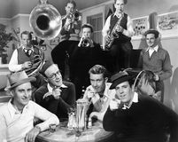 Group of men sitting in a diner with musicians behind them Stock Images
