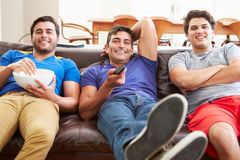Group Of Men Sitting On Sofa Watching TV Together Stock Photos