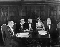 Group of men sitting with a young woman in a boardroom. (All persons depicted are no longer living and no estate exists. Supplier grants that there will be no Royalty Free Stock Photos