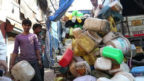 Group of men unloading products from a truck at street in Mumbai. MUMBAI, INDIA - 12 JANUARY 2015: Group of men unloading products from a truck at street in stock video