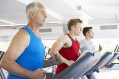 Group Of Men Using Running Machines In Gym Stock Images