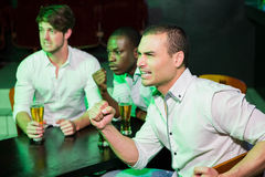 Group of men watching television in bar Stock Image