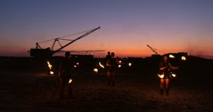 A group of men and woman fire show at night on the sand against the background of fire and tower cranes stock footage