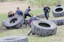 Group of men and woman struggling to tip a large tractor tire Royalty Free Stock Photo