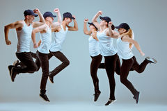 Group of men and women dancing hip hop choreography. Group of men and women dancing fitness or hip hop choreography in gray studio background royalty free stock image
