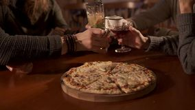 Young people are clicking glasses over plate with pizza in cafe, close-up. Group of men and women are drinking cocktails and clicking glasses in a pizzeria stock video footage