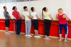 Group of  men and women practicing at the ballet barre Royalty Free Stock Photos