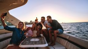 Selfie at boat party. Group of men and women relaxing on the yacht with drinks and taking selfie. Multi-ethnic friends making selfie during boat party royalty free stock image