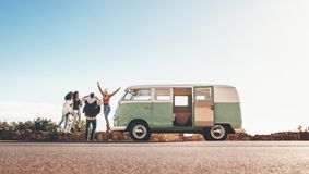 Friends on roadtrip taking pictures on highway. Group of men and women on road trip together. Old minivan parked on highway with friends taking pictures outdoors Royalty Free Stock Images