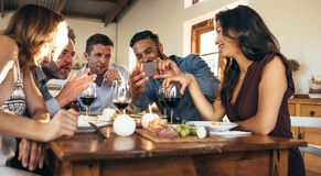 Friends at dinner party looking pictures on smartphone. Group of men and women sitting around dinner table and looking at mobile phone. Man showing pictures on Royalty Free Stock Photo