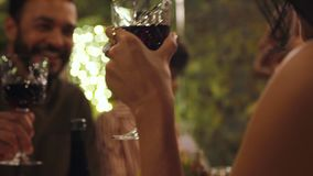 Friends at dinner party. Group of men and women sitting at dinner table and toasting drinks. Young people enjoying having drinks at dinner at backyard garden stock video