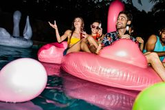 Friends enjoying pool party in evening. Group of men and women sitting on inflatable pool mattress. Friends enjoying in a pool in evening. Evening pool party Stock Image