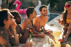 Group of friends chilling at pool party. Group of men and women talking and having drinks at pool party. Friends enjoying a summer day at poolside Stock Image