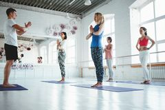 Group of men and women warming up and doing fitness training in class. Young active people are doing yoga together stock photo
