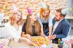 A group of men and women working in the office, eating pizza in a festive mood. Beverages. Caps on the head. Concept of a holiday in the office Stock Photography