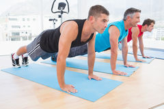 Group of men working on exercise mat Stock Image