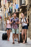Group of merry tourists with camera and map. Walking at the street Royalty Free Stock Photo