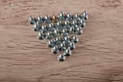 Group of metallic screws stay on wooden table. Top view Stock Photography
