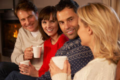 Group Of Middle Aged Couples With Hot Drinks. Group Of Middle Aged Couples Sitting On Sofa With Hot Drinks Talking Royalty Free Stock Photography