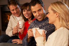 Group Of Middle Aged Couples With Hot Drinks. Group Of Middle Aged Couples Sitting On Sofa With Hot Drinks Talking Stock Images